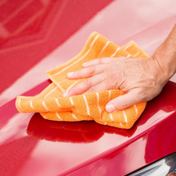 Cropped image of male worker washing red car hood